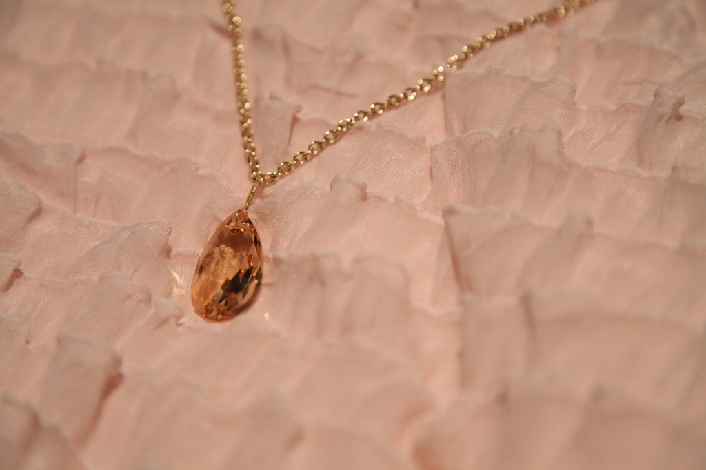 """Queen (Swarovski light topaz pear crystal pedant on a simple gold plated chain 30"""" displayed)"""
